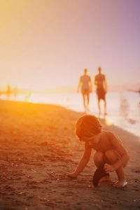 Niño recogiendo conchas junto al mar al atardecer, mientras se ven los padres al fondo