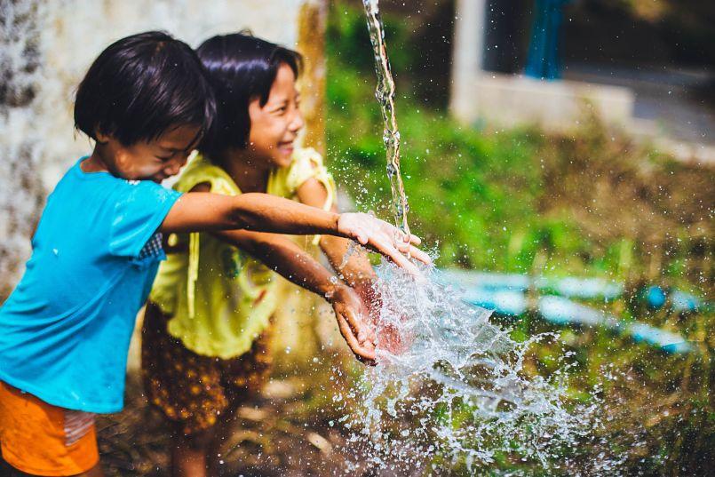 Dos niñas jugando con el agua de una fuente