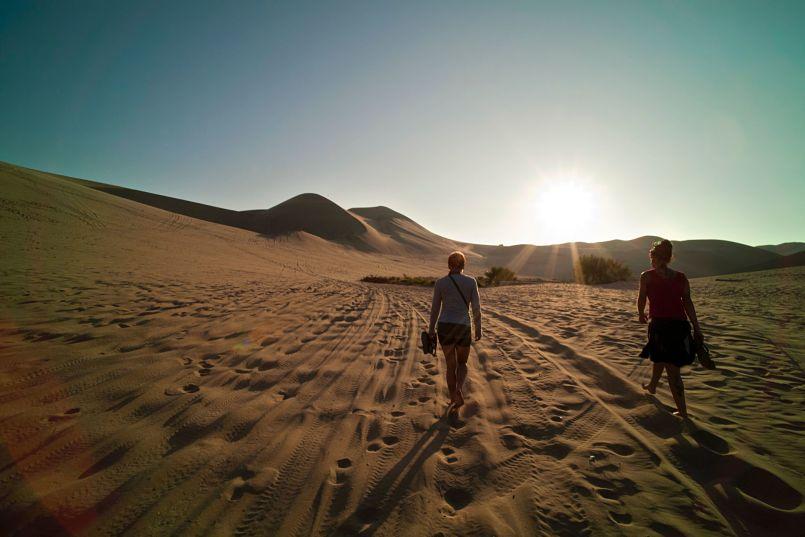 dos mujeres vistas de espaldas andando hacia el sol y dejando huellas.