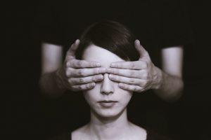 Unas manos tapan los ojos del rostro de una mujer
